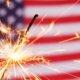 Sparkler lit up against an American Flag background